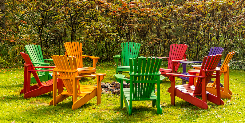 Wooden adirondack chairs arranged in a circle around a fire pit with autumn colors.
